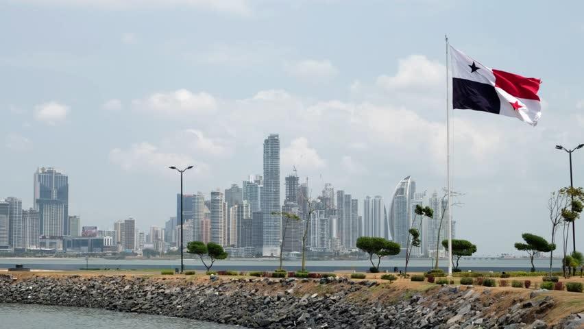 Panama City, Panama - march 2018: National flag of Panama with skyline of Panama City in background