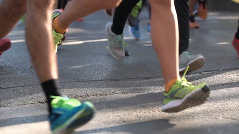 Sofia, Bulgaria - 15 Octomber 2018: Marathon running race. Legs and bodies only. Unrecognizable people. The marathon is a long-distance running race with an official distance of 42.195 km. x5 slow mo.