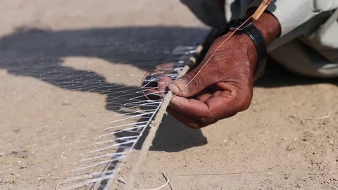 A fisherman works on creating a large net to catch fish.