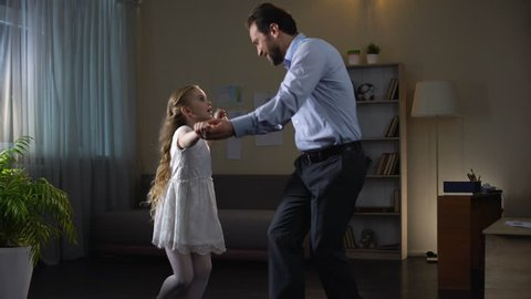 Cute girl dancing with father at home, spending time together, playing game