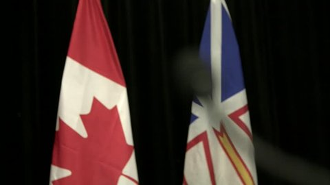 Rack focus to microphone in front of canadian flag with aboriginal flag