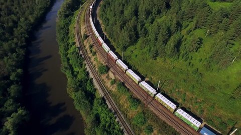 Freight train carries an electric locomotive by two-sided Trans Siberian railway along the river in the Ural Mountains - Aerial Photography, top view