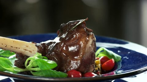 Lamb knuckle, sauce and ratatouille. Tasty meat close up.