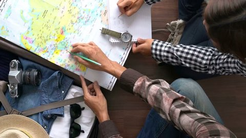 Overhead view of Traveler's Young couple planning honeymoon vacation trip with map. Top view.