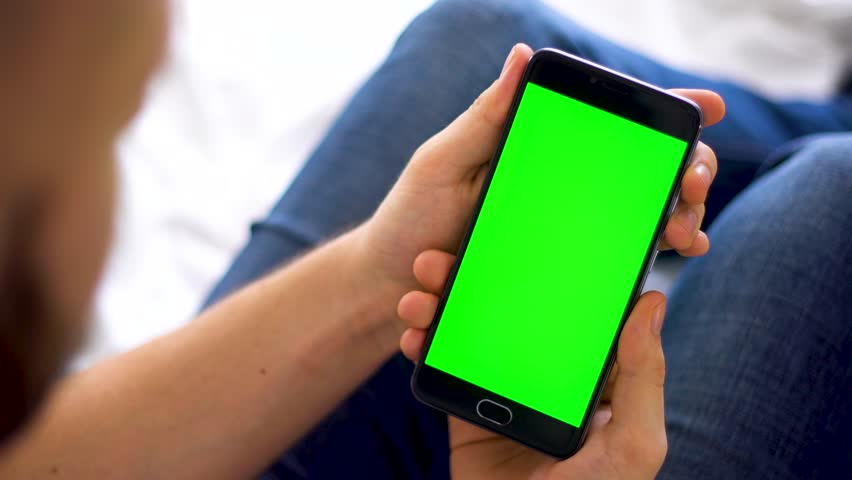 A black smartphone with green screen for chroma key compositing the hands of a man on laptop background, of Internet commerce and the use of online banking to pay for and goods in Internet, top view. #1009646378