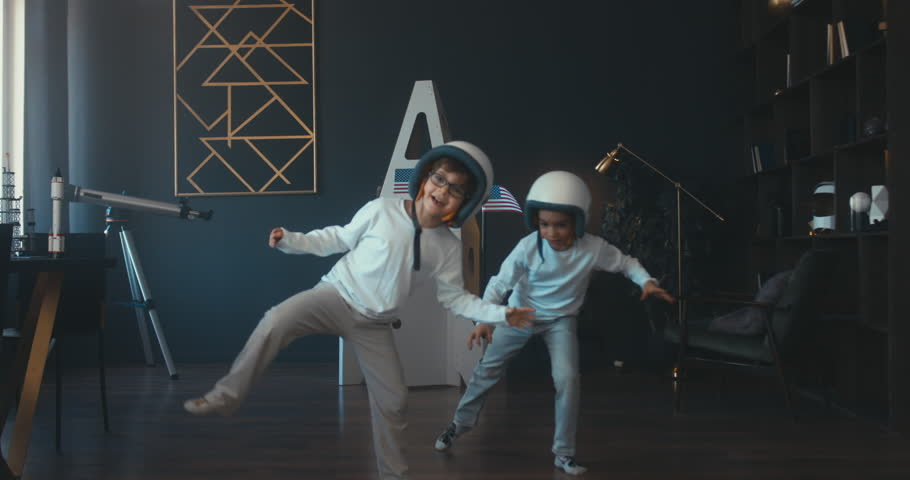 Cute little dreamer siblings boy and girl wearing space helmets pretending to be astronauts on Moon, getting out cardboard space rocket at home. 4K UHD 60 FPS SLOW MO