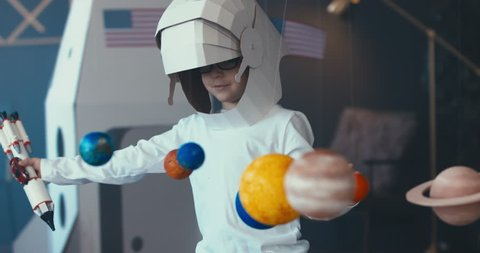 CU Cute little boy wearing cardboard astronaut helmet flying toy rocket with attached red sports roadster car to it. 4K UHD 60 FPS SLOW MO