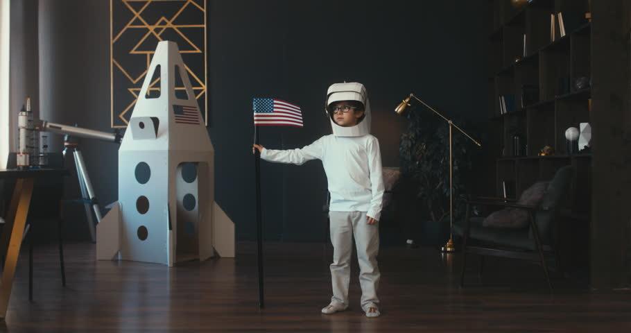 CINEMAGRAPH - seamless loop. Cute little dreamer kid boy wearing cardboard helmet pretending to be astronaut on Moon, placing US flag near cardboard space rocket at home