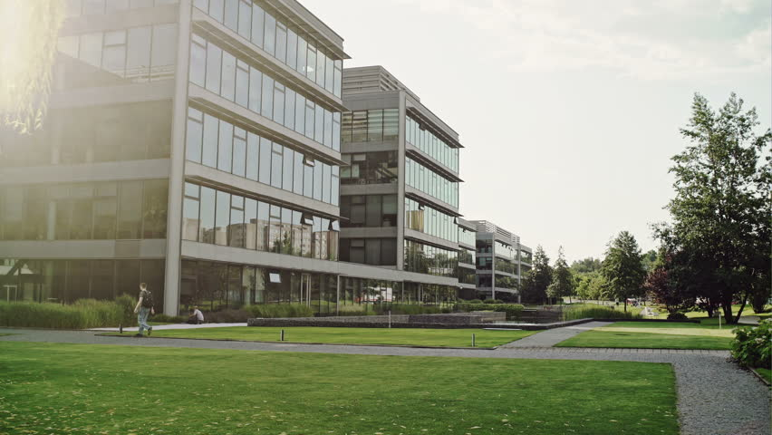 Modern office complex viewed over neat landscaped green lawns and trees with a passerby and reflections of passing traffic in the glass windows.