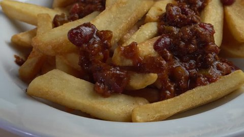 Closeup chef's hand putting chilli con carne sauce on top of the french fries chips