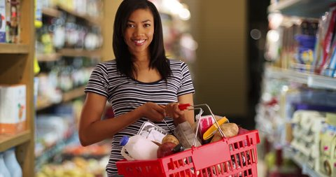 Portrait of black woman at the grocery store holding shopping basket. Young mom running errands at the supermarket smiling at camera. 4k