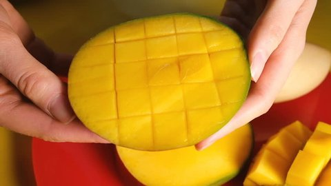 Woman opens a cut mango, slow motion