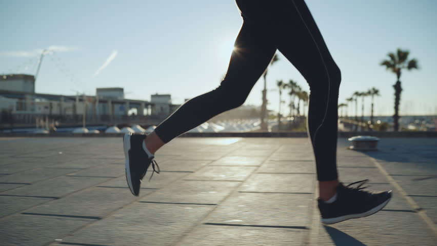 Young sportive woman running near the city beach, athletic girl jogging outdoors in the morning, slow motion | Shutterstock HD Video #1009706438