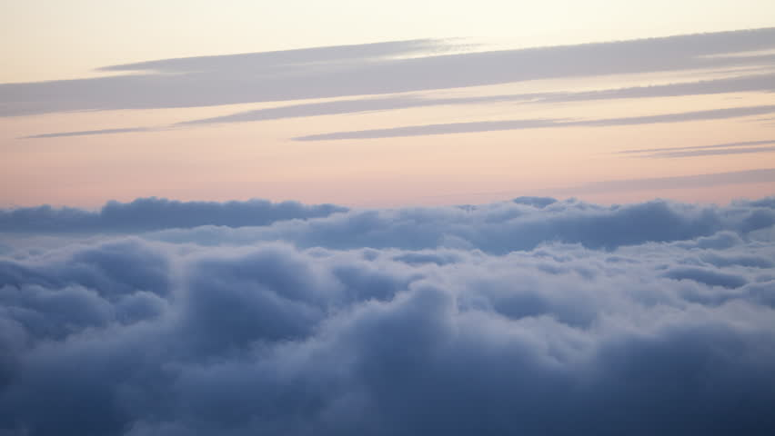 4K high altitude time lapse static shot of wispy clouds in a colorful pastel orange and yellow dusk sky above a carpet of blue, rolling, puffy inversion clouds isolated in the sky