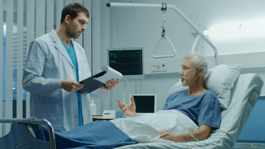 In the Hospital, Recovering Senior Patient Lying in Bed Talks with a Friendly Doctor. Modern Hospital Ward where People Get Best Health Care. Shot on RED EPIC-W 8K Helium Cinema Camera. #1009728638