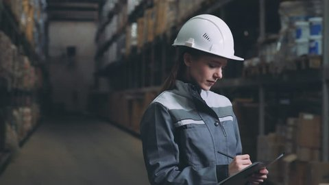 Young woman in uniform and white helmet carries out an audit in the warehouse. Warehouse worker (merchandiser) does the inventory and counts boxes. Strict employee of warehouse imaking notes.