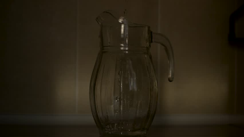 Pouring water into a carafe. Slow motion. At dawn of the day. | Shutterstock HD Video #1009742048
