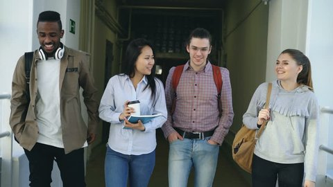 Mutli-ethnic group of male and female students are walking in big corridor of university discussing study smiling and laughing talking to each other positively