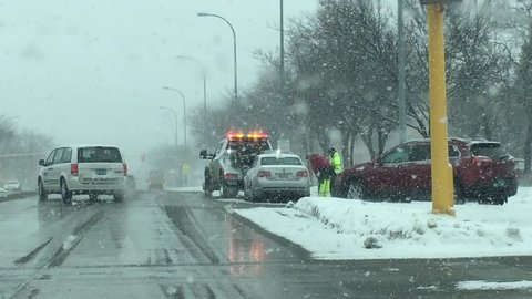 Snow storm with tow truck driver helping stranded driver on busy street.