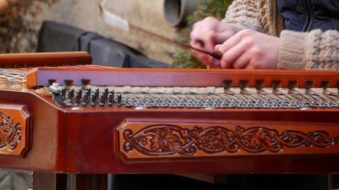 Playing the dulcimer folk musical instrument from Europe, playing the cymbals, cymbal, a young man playing cymbals, dulcimer musical instrument, Hutsul cymbals,Carpathian dulcimer