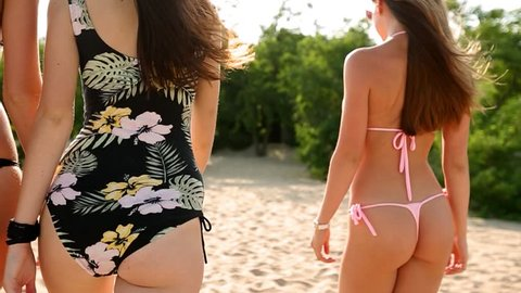 Back view of four slim women walking on tropical sandy beach near ocean. Tanned pretty girls friends wag with pretty tanned buttocks on seaside wearing swimwear and bikini on vacation in slow motion.