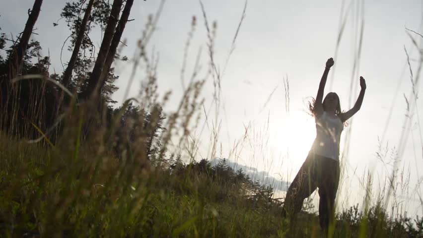 Silhouette of dancing girl in high grass