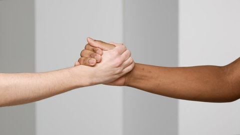 Two multiethnic men shaking hands and doing greeting gestures closeup, isolated over white background in slow motion, friendship and communication concept