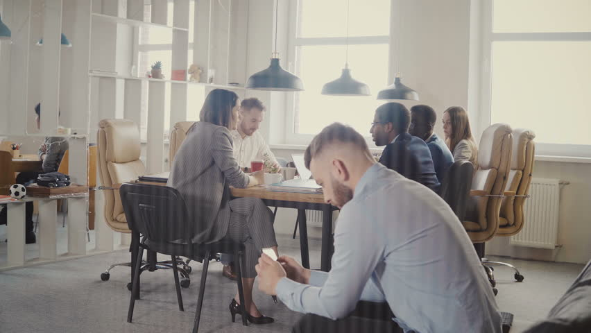 Dolly shot of multiethnic business meeting in modern office. Young successful European businessman using smartphone 4K. | Shutterstock HD Video #1009818308
