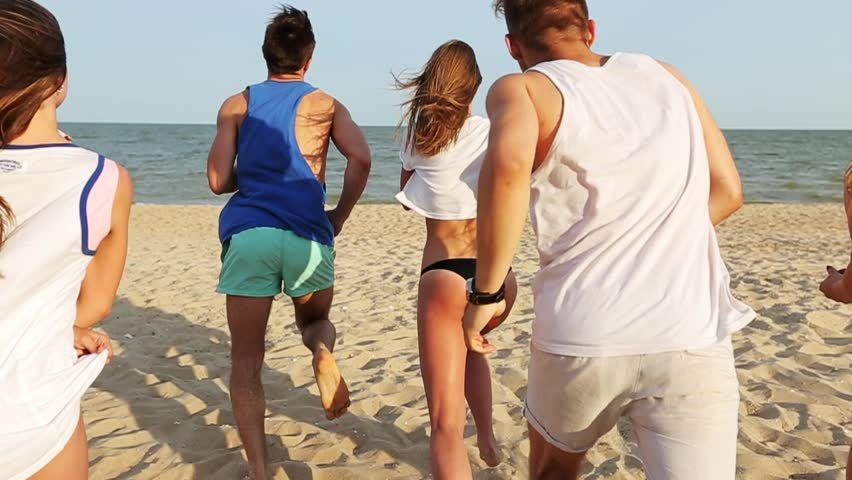 Back view of group of friends undress running into the sea water on sunset and throw shirts on the beach. Cheerful happy people having fun on the beach. Men and women go to swim in slow motion.