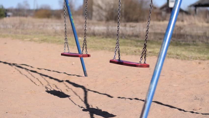 Empty Swing swinging in desolate area. Apocalyptic feel and mood.