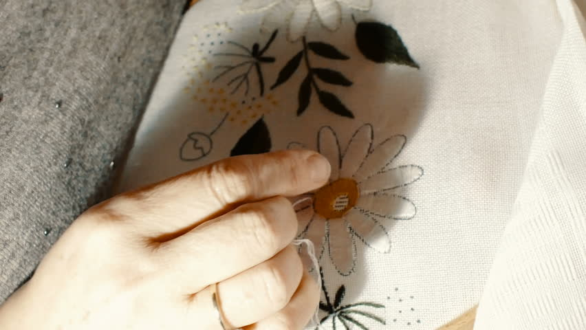 close up hand that embroiders a flower with the use of a wooden frame for embroi