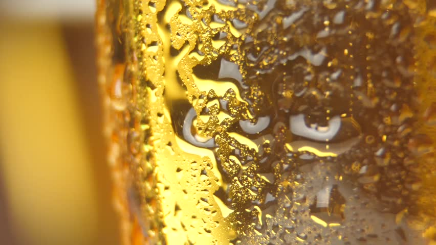 cold light beer with bubbles in a glass and dripping condensate drops