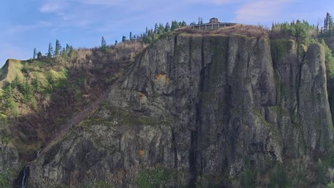 Aerial view in the Columbia River Gorge of the cliffs  at Vista House moving left revealing the massive moss covered cliffs SS
