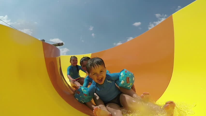 Funny little boys and girls roll with yellow water slides | Shutterstock HD Video #1009892078