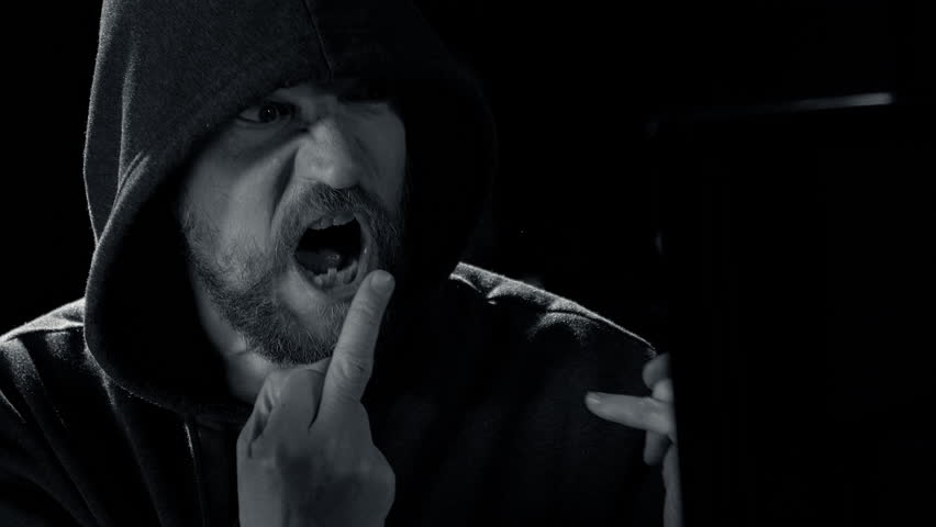 Angry man with hood screaming towards screen showing finger black and white