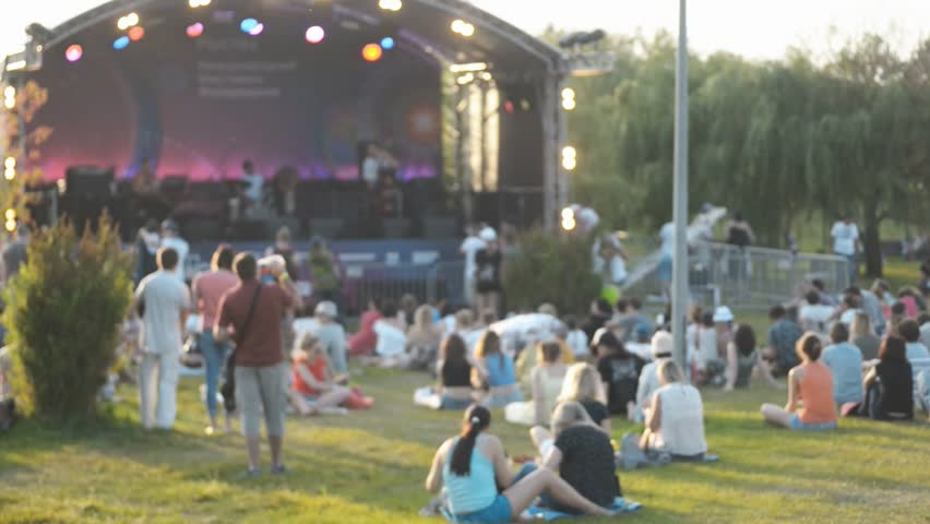 Celebratory concert and watching people outdoors on summer day. Singing artists on stage, men women stand and sit on grass in warm weather, next to green trees. Festive event is in open air, people | Shutterstock HD Video #1009909508