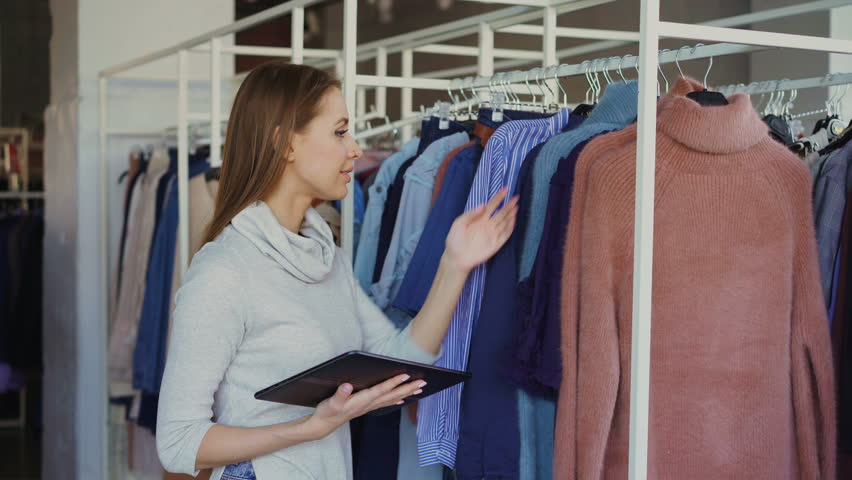 Owner of women's clothing shop is checking and counting garments on rails while using tablet. She is typing information about her goods. Small business concept. | Shutterstock HD Video #1009917098