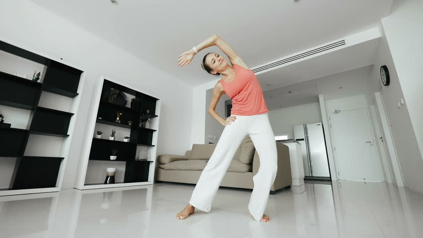 Sporty woman training morning workout in home interior. Young woman doing gym workout in home. Healthy and sport lifestyle
