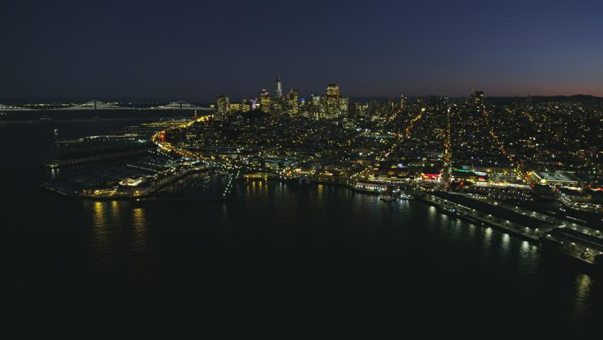 Aerial illuminated night cityscape view of Fishermans Wharf Pier 39 North Beach San Francisco city skyscrapers Oakland Bay bridge California USA