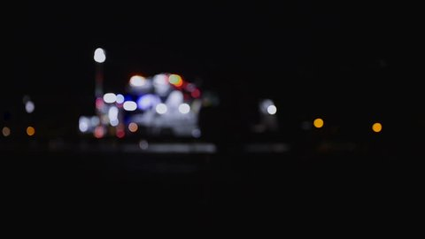 Highway accident with fire trucks and towing truck clearing wreckage, out of focus, night scene