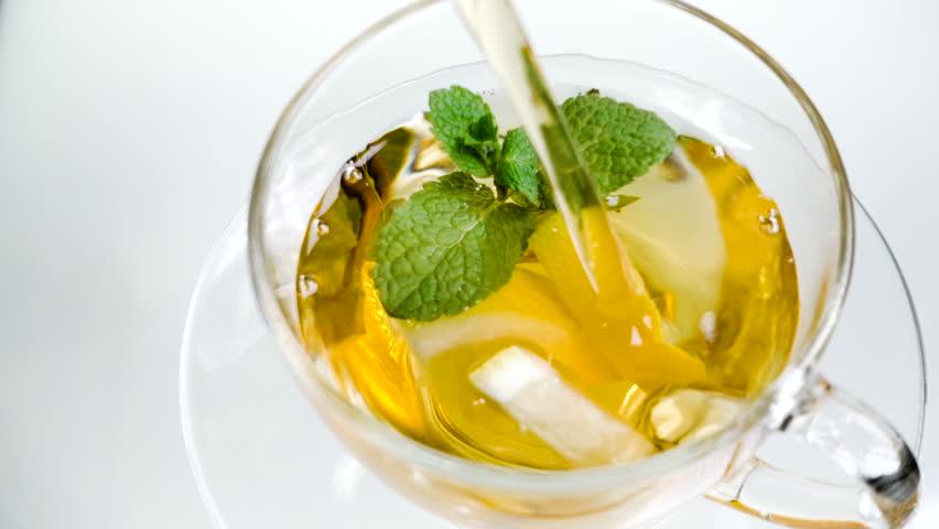 Hot herbal tea with ginger, lemon and mint. Ginger beverage in transparent teapot. Healthy lemon tea.