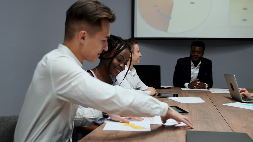 A group of creative multi-ethnic managers disassemble at the meeting of the board of directors in the conference hall the graphs of profit for the last year in the firm. An African American girl and a   Shutterstock HD Video #1009936058