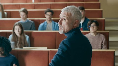 Camera Facing Class: Prominent Professor Writing on the Blackboard and Giving Lecture to a Classroom Full of Multi Ethnic Students. Modern University with Bright Young People in the Lecture Hall.