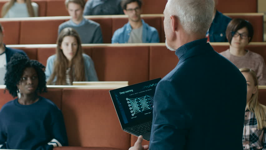 Back View of the Professor Giving Lecture on Computer Science to a Classroom Full of Multi Ethnic Students. Teacher Holds Laptop with Deep Learning, Artificial Intelligence Infographics on the Screen. | Shutterstock HD Video #1009951958