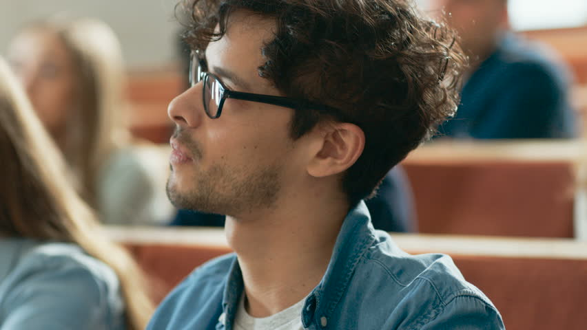 Handsome and Smart Hispanic Man Listens to a Lecture in a Classroom Full of Multi Ethnic Students. Shallow Depth of Field.  Shot on RED EPIC-W 8K Helium Cinema Camera.