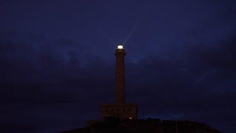 Stone lighthouse on hill casting light beams against a blue twilight sky.