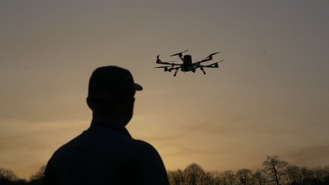 Man silhouette drone control at sunset. Dark silhouette against colorfull sunset. Soft focus