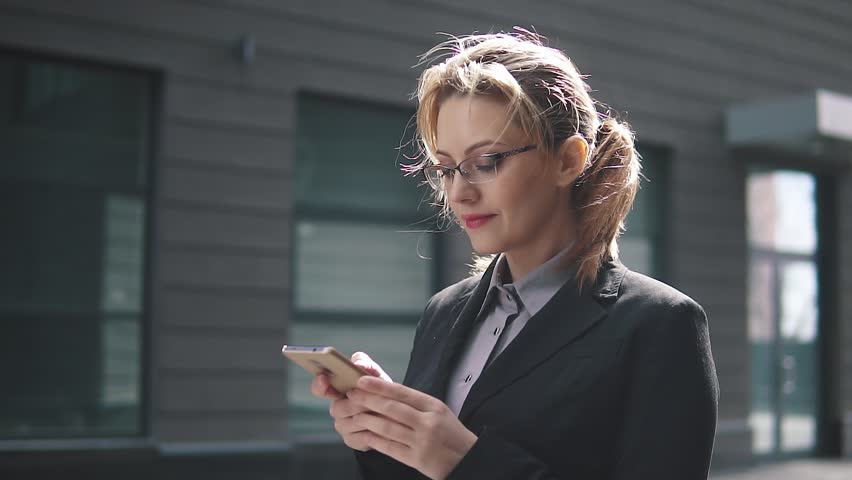 The girl in a business suit sends a texting on mobile phone. the wind in your hair   Shutterstock HD Video #1009964468