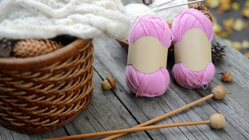 Two pink balls of wool threads with empty labels lying on vintage wood desk with knitting needles and basket. Mock up background for your craft knitting logo or label   Shutterstock HD Video #1009966028