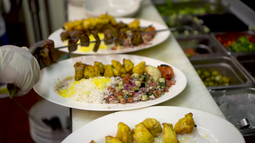 Chef slides beef kabob off of a skewer onto a plate with chicken kabob and rice with saffron.